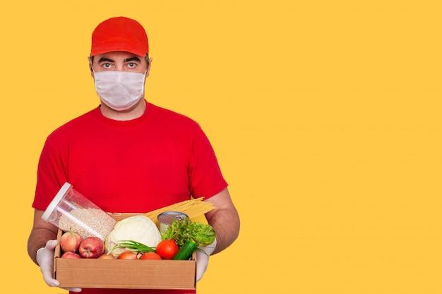 Een koerier werknemer in uniform houdt een kartonnen doos met voedsel, masker dragen, coronavirus concept