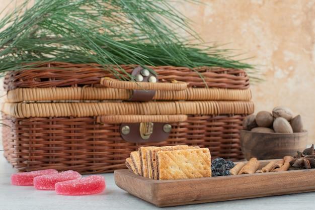 Een koffer en een houten bord vol met crackers, steranijs en kaneelstokjes op marmeren achtergrond. hoge kwaliteit foto