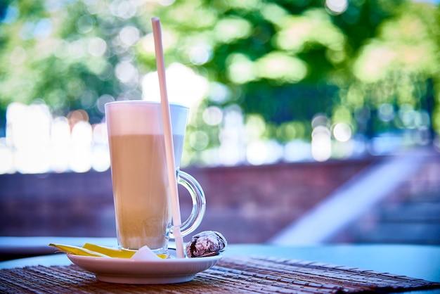 Een koffiedrank in een glas op een schotel met koekjes