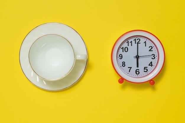 Een koffiekop en schotel en een rode wekker op een gele achtergrond. het concept van het opheffen van de toon in de ochtend. plat leggen.