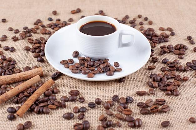 Een koffiekopje met koffiebonen en kaneelstokjes