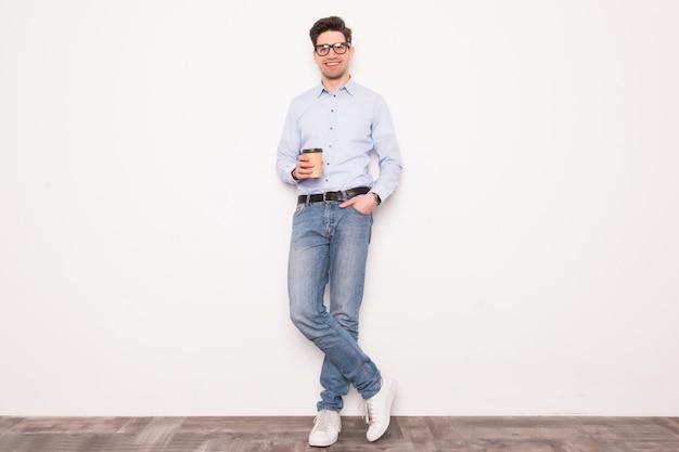 Een koffiepauze nemen. knappe de koffiekop van de jonge mensenholding en het glimlachen terwijl status tegen witte ruimte
