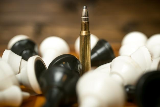 Een kogel tussen liggende schaakstukken. concept van militaire macht