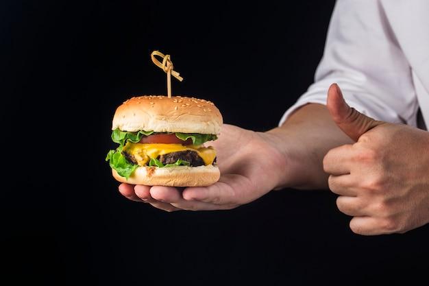 Een kok houdt een heerlijke runderhamburger vast die zojuist is gemaakt