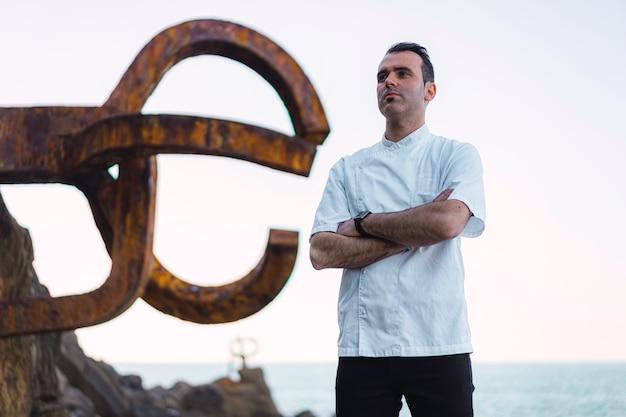 Een kok in een wit schort afgebeeld op de kust