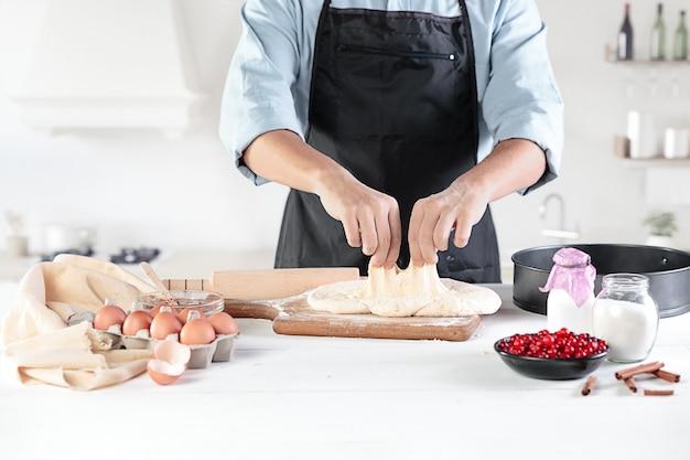 Een kok met eieren op een rustieke keuken tegen de achtergrond van mannenhanden