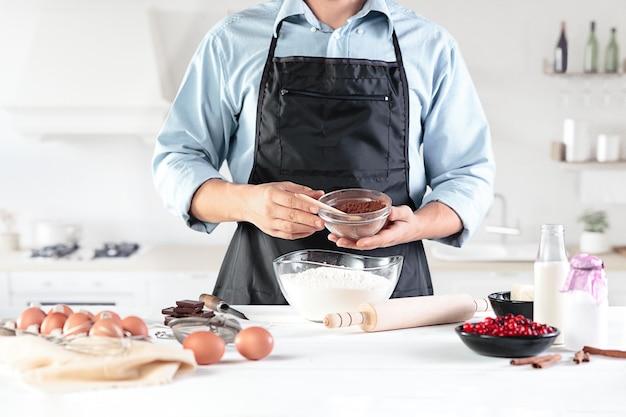 Een kok met eieren op een rustieke keuken tegen de muur van mannen handen
