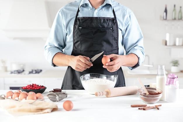 Een kok met eieren op een rustieke keuken