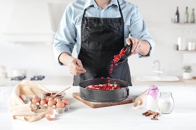 Een kok op een rustieke keuken. de mannelijke handen met ingrediënten voor het koken van meelproducten of deeg, brood, muffins, taart, cake, pizza