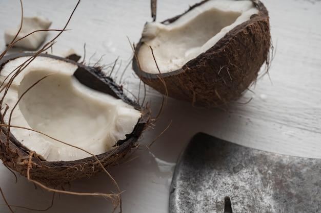 Een kokosnoot wordt in tweeën gesneden op een lichte houten tafel bovenaanzicht