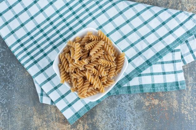 Een kom bruine fusilli pasta, op de handdoek, op het marmeren oppervlak.