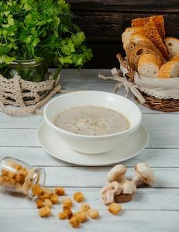 Een kom champignonsoep geserveerd met broodvulling, korriander op pot