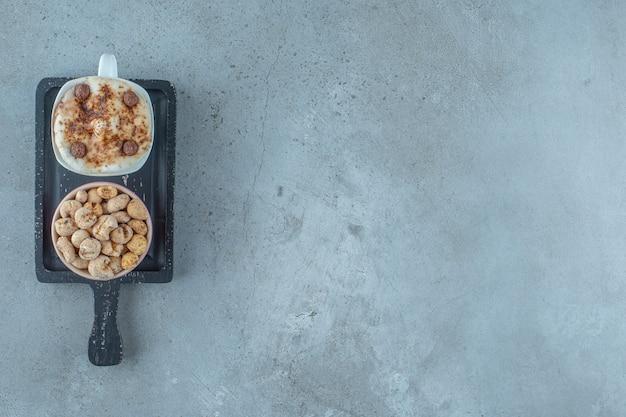 Een kom cornflakes en een kopje cappuccino op een bord, op de blauwe achtergrond.