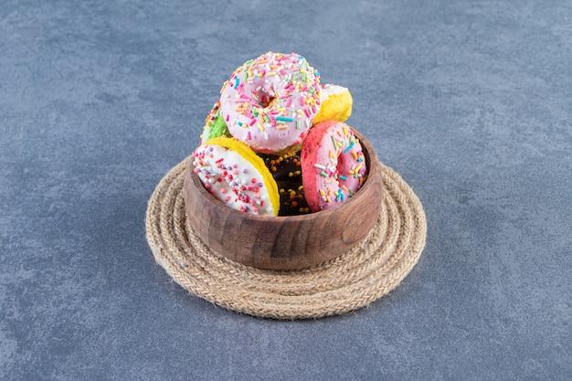 Een kom donuts op een onderzetter, op de marmeren achtergrond.