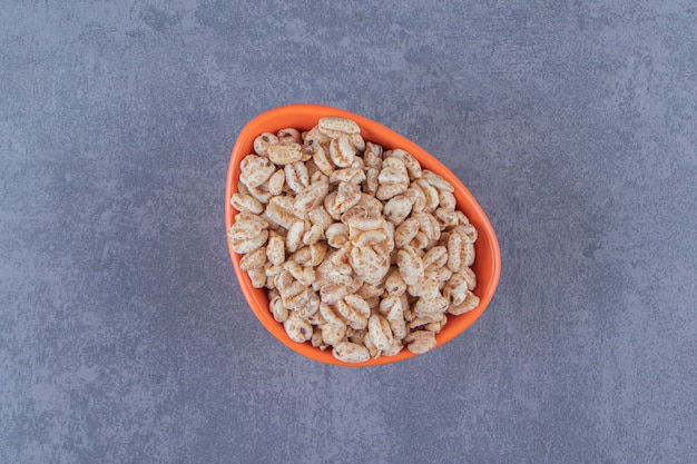 Een kom droge cornflakes, op de blauwe achtergrond. hoge kwaliteit foto