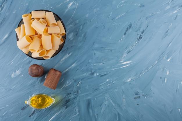 Een kom droge ruwe buisdeegwaren met olie en kruiden op een blauwe lijst.
