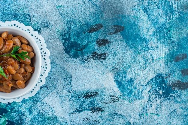 Een kom gebakken bonen op een onderzetter, op de blauwe tafel.