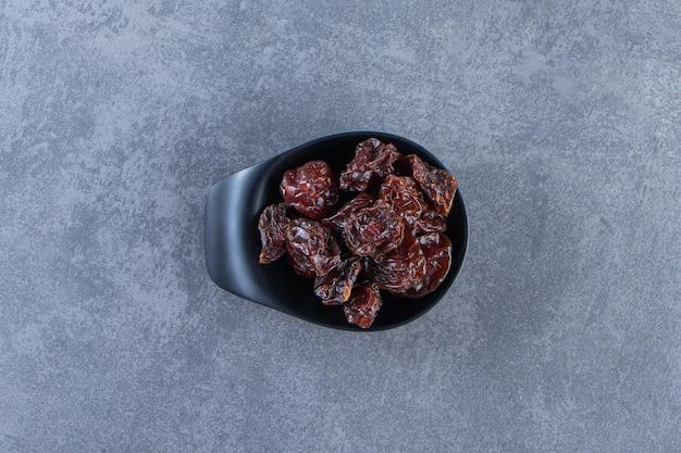 Een kom gedroogde pruimen, op de marmeren achtergrond.