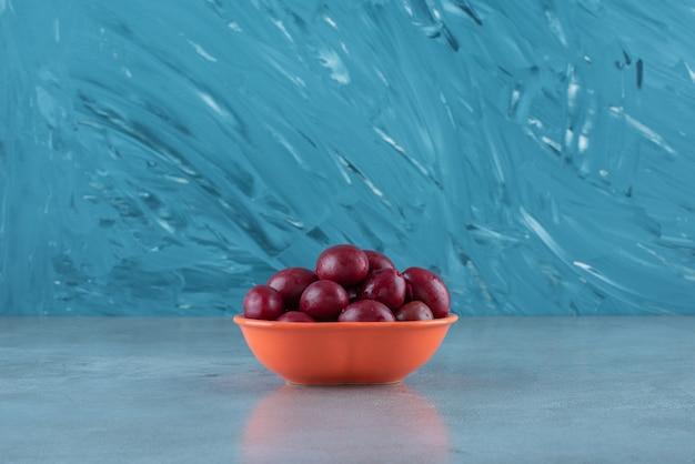 Een kom gefermenteerde pruimen, op de marmeren tafel.