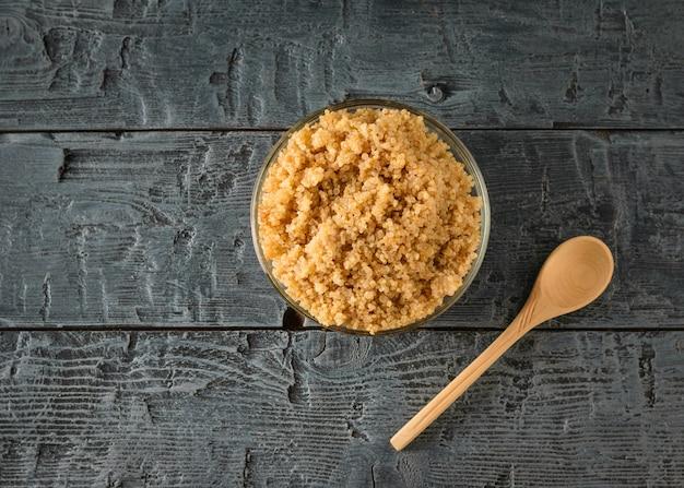 Een kom gekookte quinoa en een lepel op een zwarte tafel. een glutenvrij gerecht met gekookte granen. gezond vegetarisch dieet. het uitzicht vanaf de top. plat leggen.