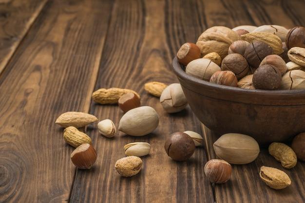 Een kom gevuld met een selectie van verschillende noten op een bruine houten tafel