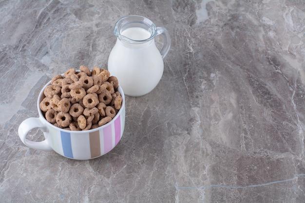 Een kom gezonde chocoladegranenringen met een glazen pot melk.