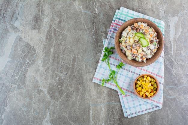 Een kom groentesalade naast een maïssalade in een kom op theedoek op marmer.
