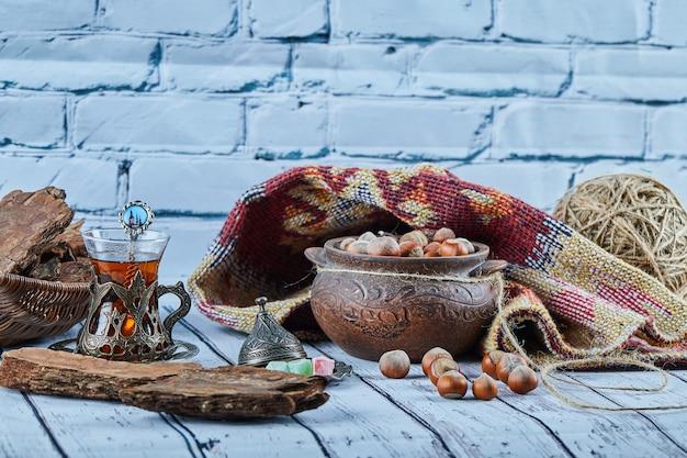 Een kom hazelnoten op blauwe houten tafel met gebeeldhouwd tapijt