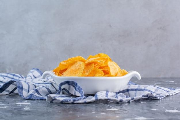 Een kom heerlijke chips op een theedoek, op het marmeren oppervlak