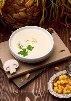 Een kom heerlijke zelfgemaakte crème van champignonsoep met geroosterd brood.