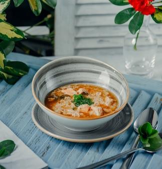 Een kom hete soep met in blokjes gesneden groene ui in moderne kom