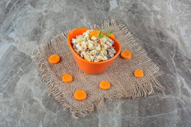 Een kom hoofdsalade naast gesneden wortel op handdoek op blauw.