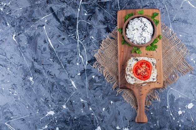 Een kom kaas naast gesneden tomaten op een kaasbrood op snijplank op jute servet, op de blauwe.