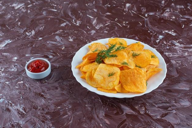 Een kom ketchup en frietjes in een bord, op de marmeren tafel.