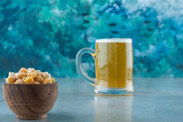 Een kom kikkererwten en een glas bier, op de marmeren tafel.