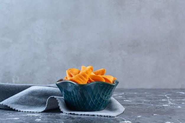 Een kom knapperige chips op een stuk stof, op het marmeren oppervlak