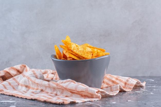 Een kom knapperige, pittige aardappelchips, op het marmeren oppervlak