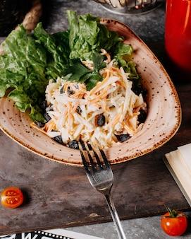 Een kom koolsla salade met zwarte rozijnen en sla