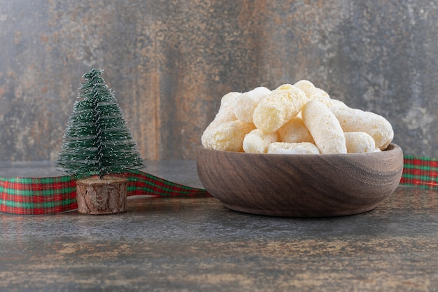 Een kom maïs snacks met kerstversiering op marmeren oppervlak