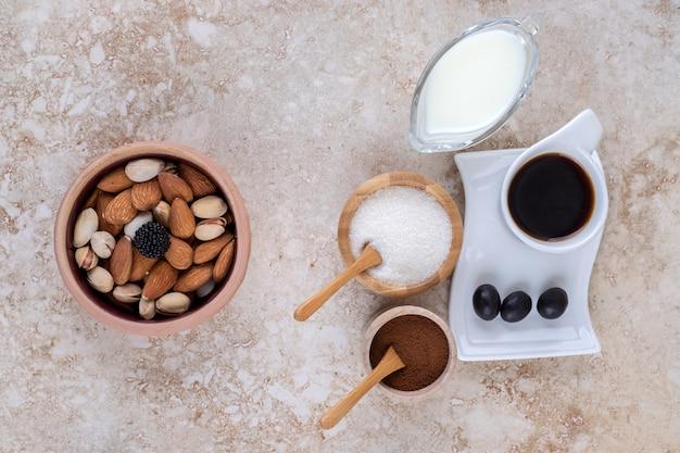 Een kom met diverse noten, kleine schaaltjes melk, gemalen koffie, suiker en een kopje koffie