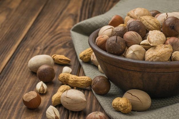 Een kom met een groot aantal noten op een doek op een houten tafel