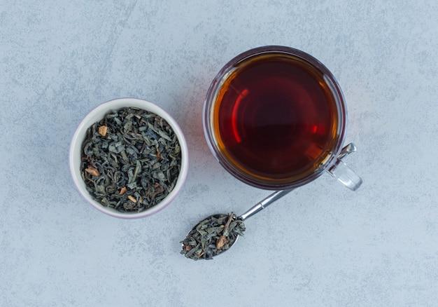 Een kom met gedroogde theeblaadjes en een kopje thee met een lepel op marmer.