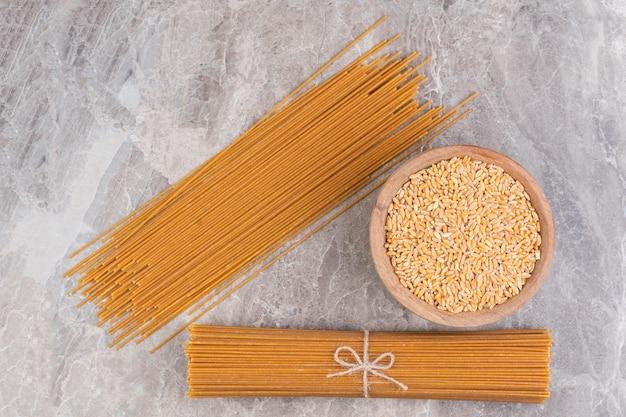 Een kom met graan en spaghetti, op het marmer.