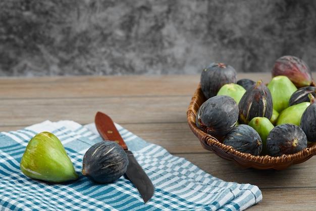 Een kom met groene en zwarte vijgen op houten tafel met een mes en een tafelkleed.