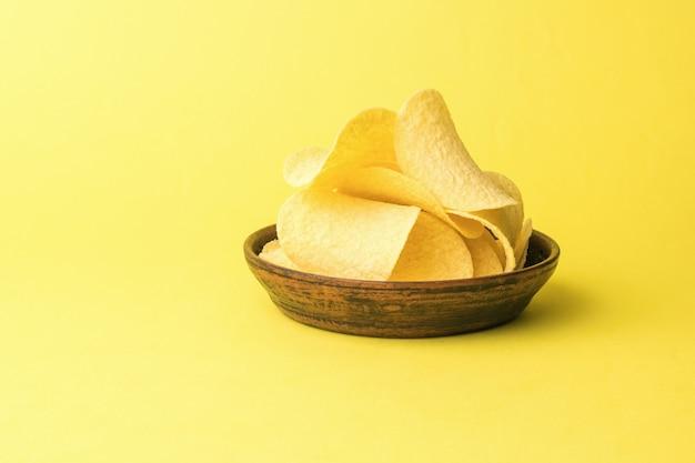 Een kom met grote chips op een gele achtergrond.