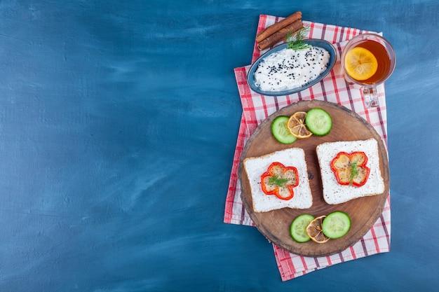 Een kom met kaas, een glas thee naast kaasbrood, gesneden citroen en komkommer op een bord, op het blauw.