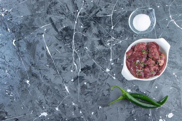 Een kom met kippenafval naast peper, op de marmeren achtergrond.