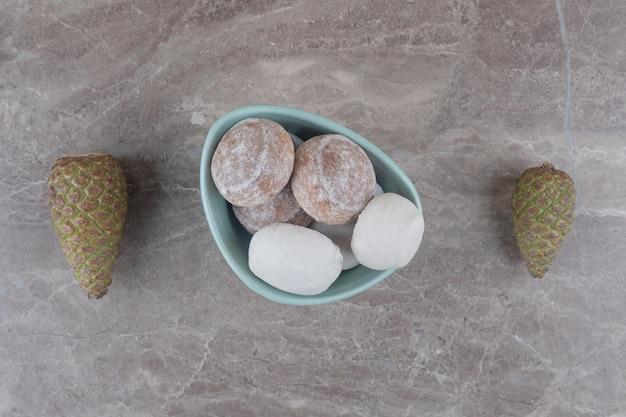 Een kom met koekjes naast dennenappels op marmer