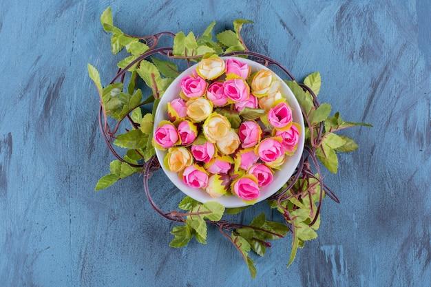 Een kom met kunstmatige kleurrijke rozen op blauw.