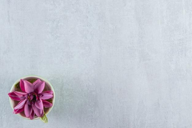 Een kom met paarse bloem, op de witte tafel.